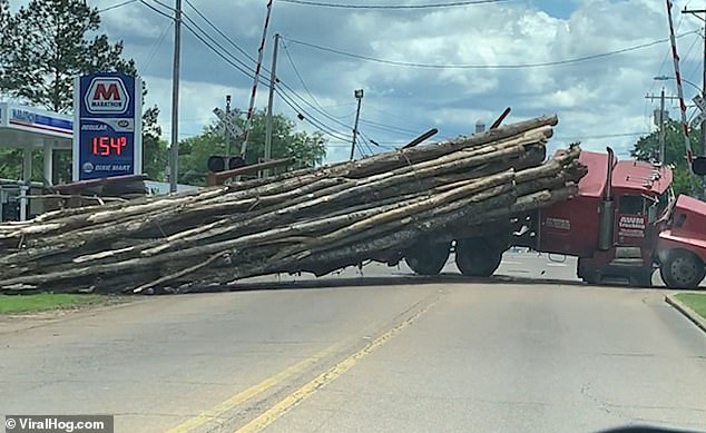 A red timber truck tips over and spills its load onto a road in Louisville, Mississippi, after attempting a tight turn and overbalancing