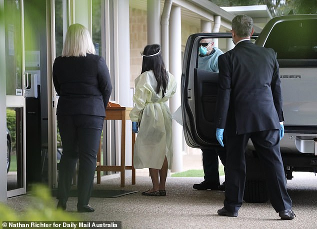 Ms Caisip (pictured) was surrounded by security guards after she was escorted from hotel quarantine to view her father's body