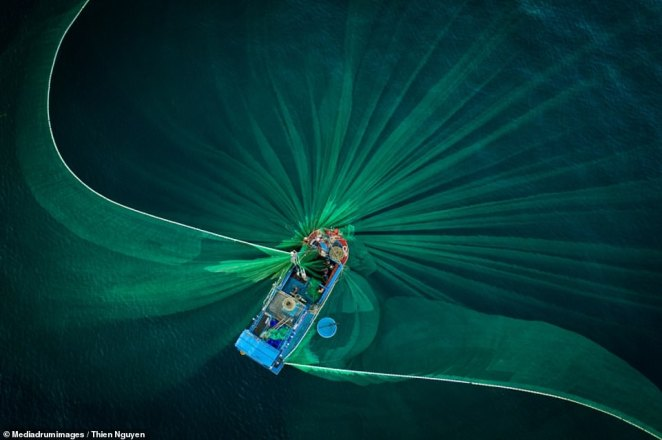 'Dancing Nets' by Thien Nguyen. A drone shot of fishermen casting their nets in a circle around their boat
