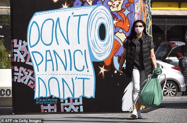 A face mask-clad woman passes a pandemic-related mural in the Melbourne suburb of Prahran on Thursday. Victorian health authorities has confirmed 136 deaths in the past 10 days - while Sweden has averaged just one life lost per day during that period