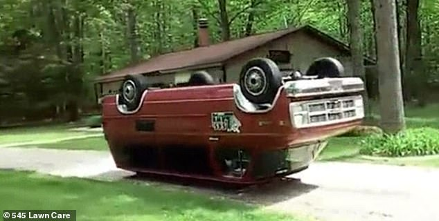 A customized red 1985 GMC van drives upside down and backwards along a driveway in Michigan