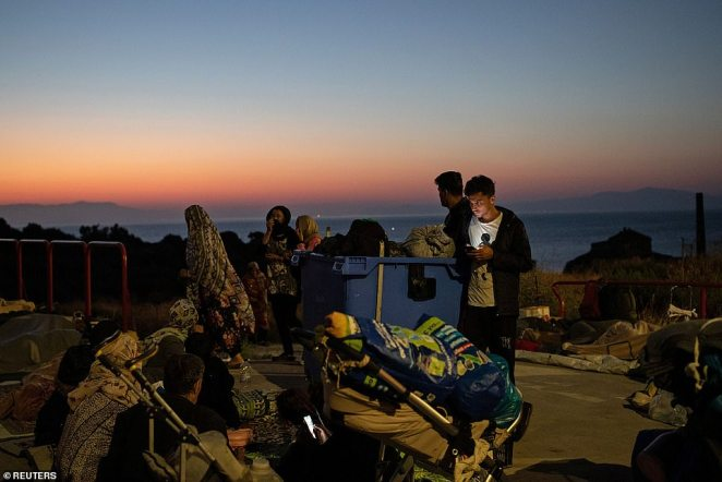 Refugees find shelter near the Lesbos coast early this morning, with thousands of people left homeless and hungry by the fire