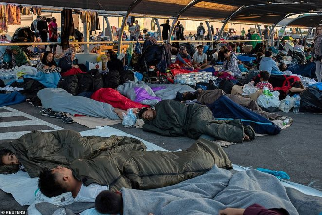 Displaced migrants sleep in a supermarket car park early today following the fire which destroyed Greece's largest refugee camp