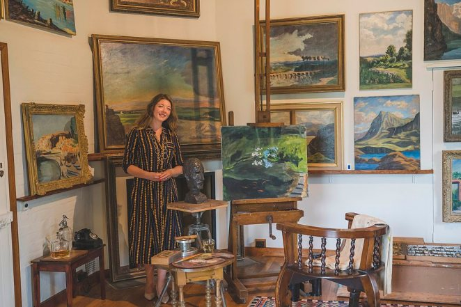 National Trust House and Collection manager Katherine Carter pictured in the redisplayed studio showing Churchill's paintings. She said the recreation 'enables us to have a deeper understanding of him as an artist'