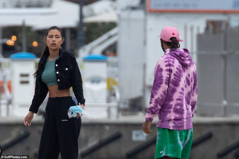 Intense: The pair seemed deep in conversation as she left the boat carrying a wad of face masks in her hand