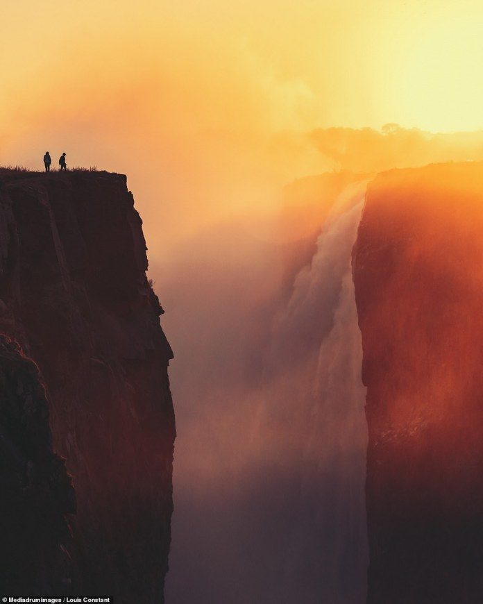 'Mosi-oa-Tunya' by Louis Constant. Two trekkers look over at Victoria Falls, the largest waterfall in the world, between Zimbabwe and Zambia. The mist from the waterfall is seen rising into the sunset, the name for the waterfall in the local Lozi language is 'Smoke that Thunders'