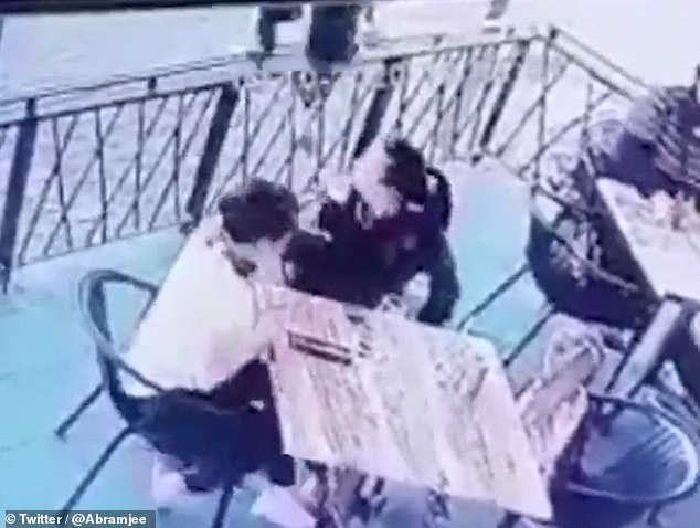 As the women turn their heads, the attacker leaps over the rails of the restaurant and jumps in to snatch the child