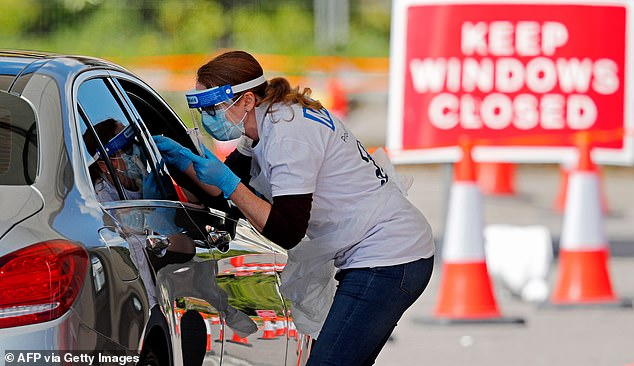A snap survey by Daily Mail reporters reveals the full extent of Covid testing chaos. Pictured, a medical worker takes a swab to test for Covid-19 at a drive-in testing facility in Chessington