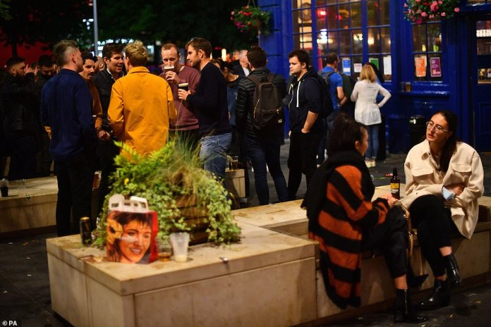 People gather outside the The Shipwrights Arms near London Bridge in London tonight for a final night out before the rules hit