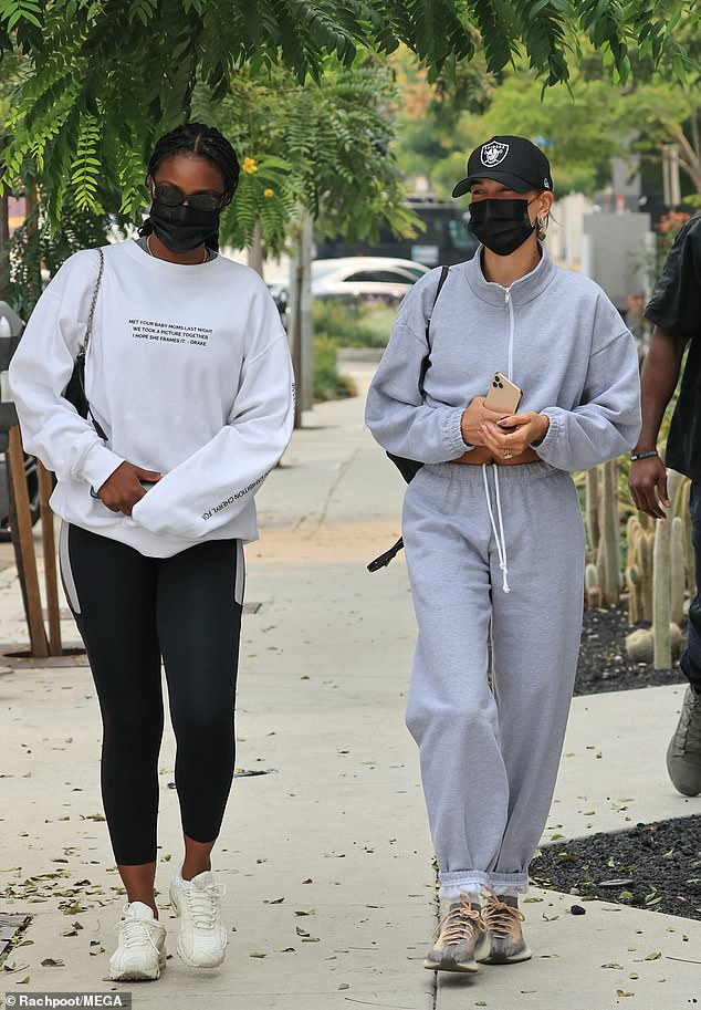 Twin masks: Justine's braids were fastened back in a low ponytail, and she covered up with sunglasses and a black face mask similar to Hailey's