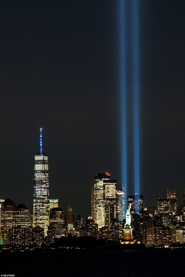 The Statue of Liberty and One World Trade Center are seen as homage at the Light Shine in downtown Manhattan
