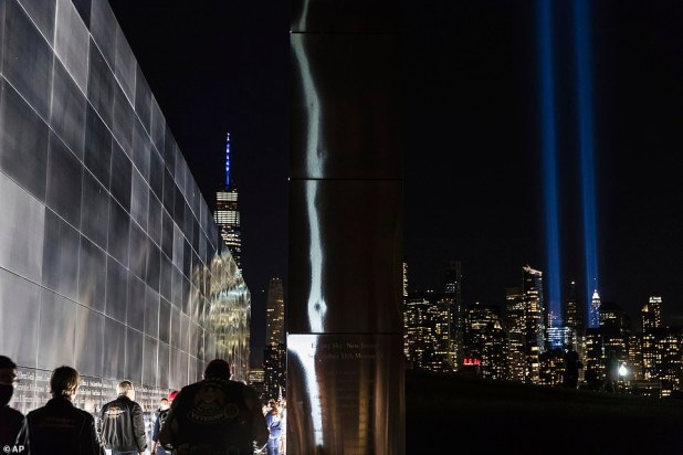 People take time to watch the tribute on the 19th anniversary of the attacks, as seen from Jersey City across the Hudson River