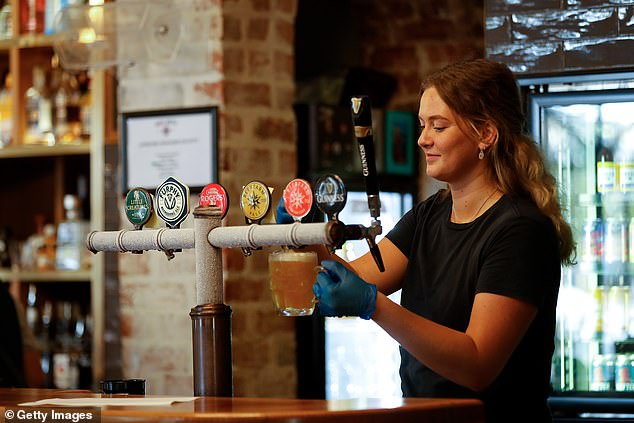 A young bartender pours a beer at the Rose Hotel in Bunbury, WA where COVID restrictions have almost completely eased