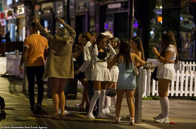 A large group of women are seen on a night out in Cardiff, just days before such gatherings will be banned under new laws