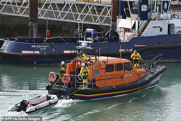 Migrants picked up at sea while crossing the English Channel are brought into the Marina in Dover on an RNLI lifeboat yesterday