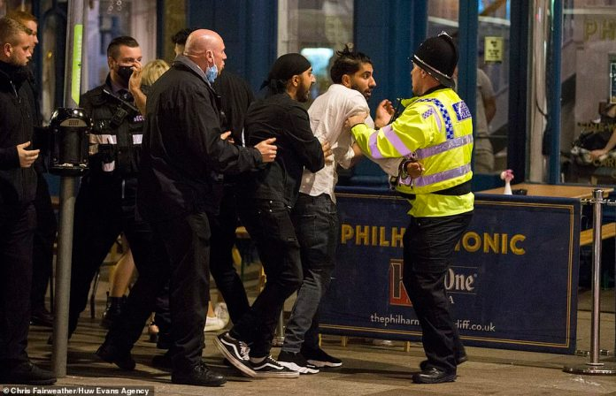 A man grapples with police and security outside a bar in Cardiff on the last weekend before 'rule of six' laws come into force