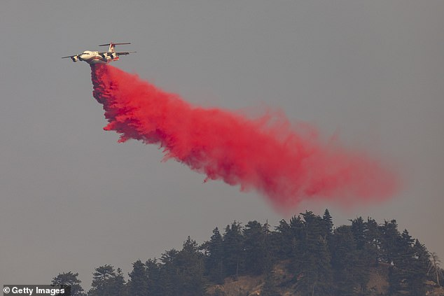 A firefighting jet tanker drops fire retardant on the Bobcat Fire at the Angeles National Forest on Friday