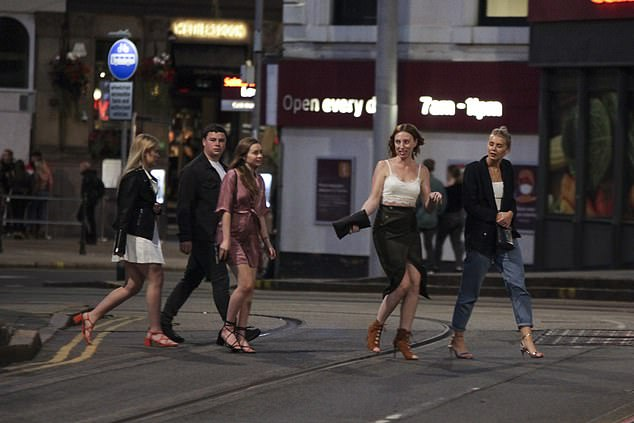 People can be seen heading out for one last night out before new coronavirus rules come into play on Monday. Pictured: Revellers in Nottingham on Friday