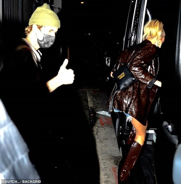 Mask up: Justin saw a thumbs up as he wore a flannel and green beanie as they headed through the luxury bus to continue their night