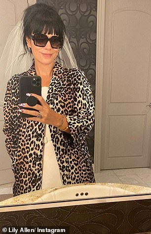 Stunning: Singer Smile looked stunning herself as she posed for a series of mirror selfies in her veil and dress, which she covered in a leopard-print coat