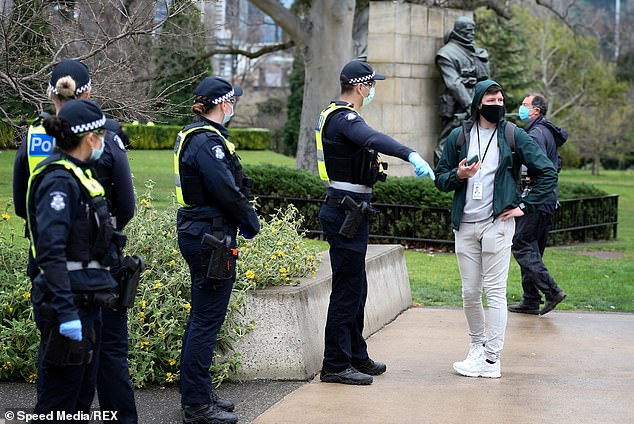 Police direct a man to move away during the Freedom Walk rally in Melbourne on Saturday morning