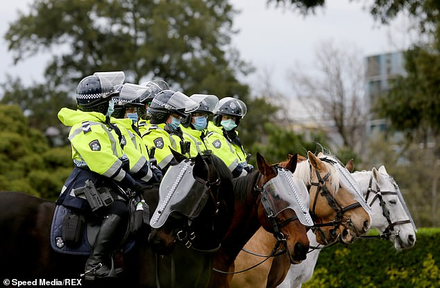 Police on horseback are seen during the Melbourne Freedom Walk rally on Saturday