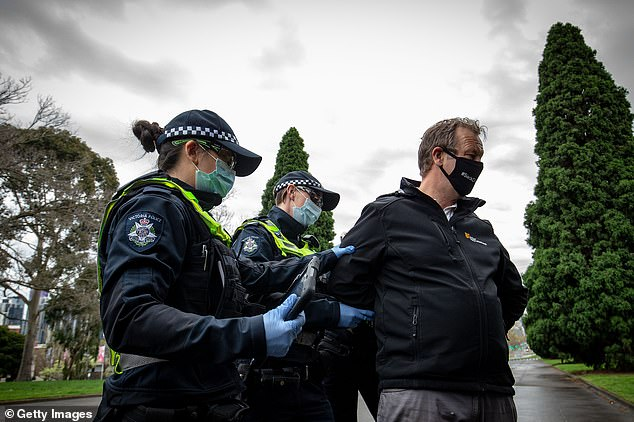 Police detain a man during the protest on Saturday. Demonstrators claimed the march was legal but police will fine anyone they suspect of breaching coronavirus restrictions