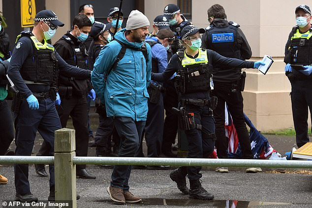 Another demonstrator is taken away in handcuffs by police. Victoria recorded 37 new coronavirus cases on Saturday