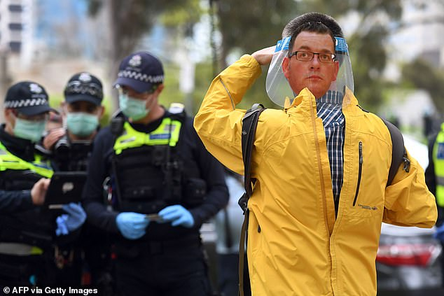 A man wears a face shield with Mr Andrews' head on the back while speaking to police at the march