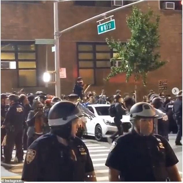 Police wearing face shields and helmets forced back the protesters from the precinct