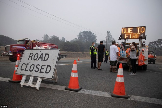 Berry Creek residents speak with authorities at a road block after the Bear Fire, part of the North Complex fires, passed through in Berry Creek, California, on Saturday