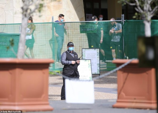 Pictured: Security personnel manning the hotel while people mill around freely in the background