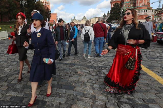 Women in costumes and vintage outfits strolled through the streets next to members of the public as they attended the car rally