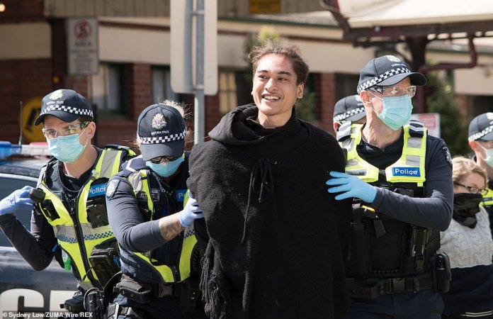 A man smiled as several gloved and masked police arrested him during the second day of protests in Victoria's capital city