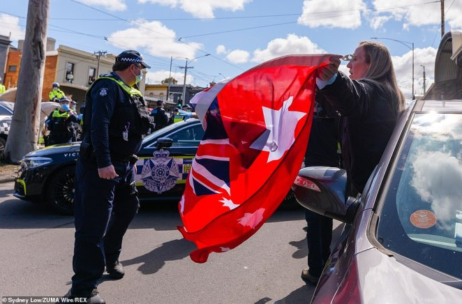 A protester waves a red ensign flag at officers as police swarmed Melbourne's CBD where up to 250 people amassed at the Queen Victoria Markets