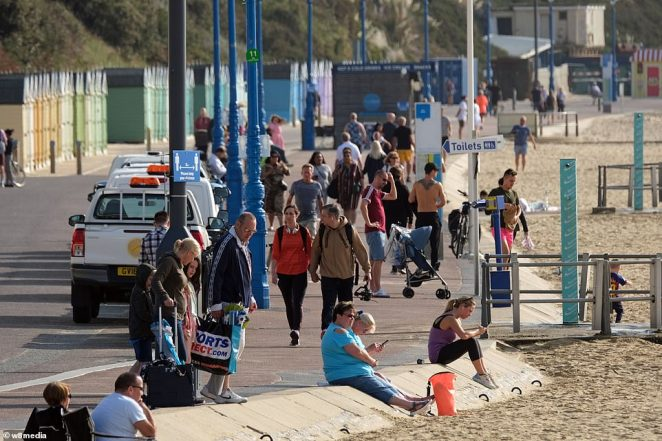 People walk along Bournemouth beach just a day before the Prime Minister Boris Johnson's 'rule of six' rule is brought in