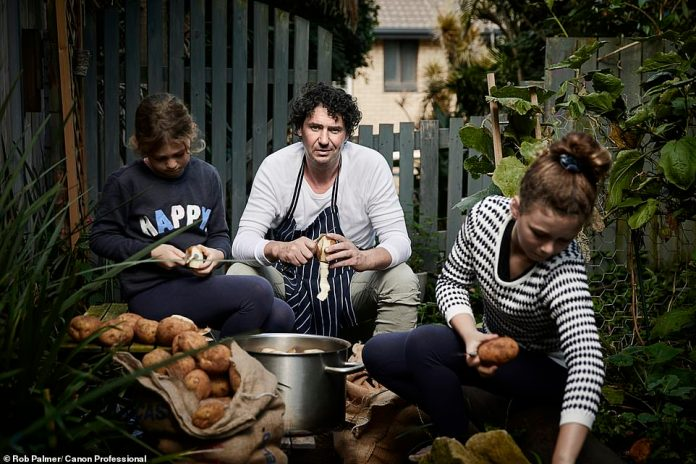 Chef Colin Fassnidge photographed during the restaurant closures. He is pictured peeling potatoes with his two daughters in preparation for the evening's soup kitchen