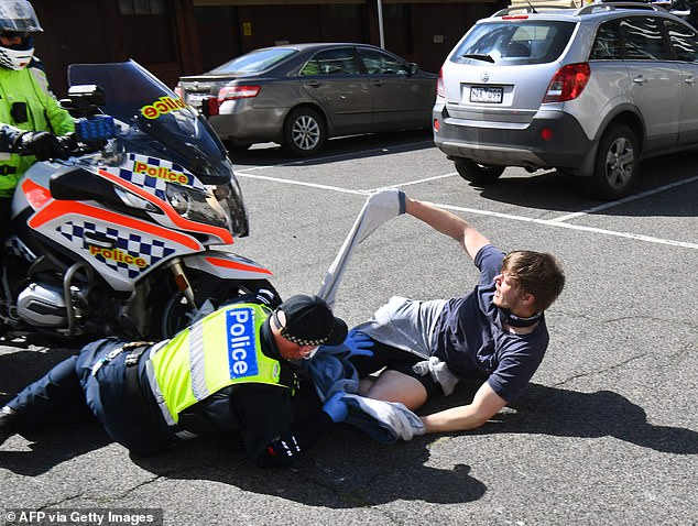 A police motorcycle rider could be seen knocking an anti-lockdown protester to the ground as tensions escalated over the Victorian government's strict coronavirus restrictions
