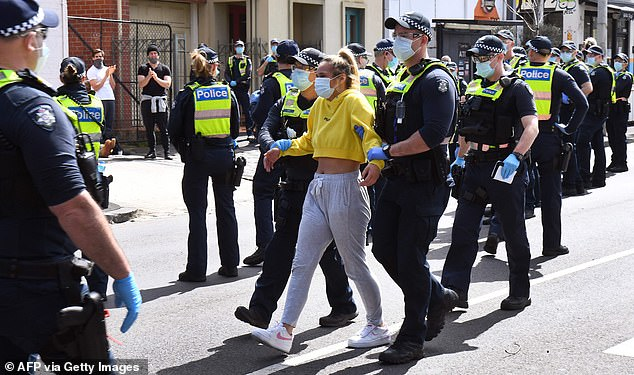 Pressure is rising as hundreds took to Melbourne's streets for a second day in a row to protest. Pictured: a protester is detained at Melbourne's Queen Victoria Market on Sunday