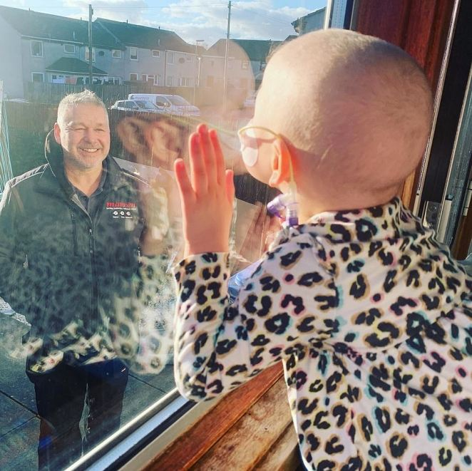 Shielding Mila by Lynda Sneddon. A child wearing medical support equipment is seeing looking out of a window