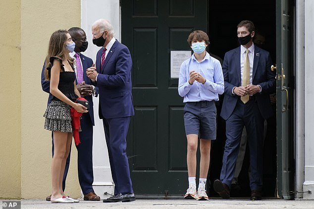 Biden attended mass at the church earlier in the day and returned for the confirmation ceremony. Pictured wearing a mask and speaking with Natalie left