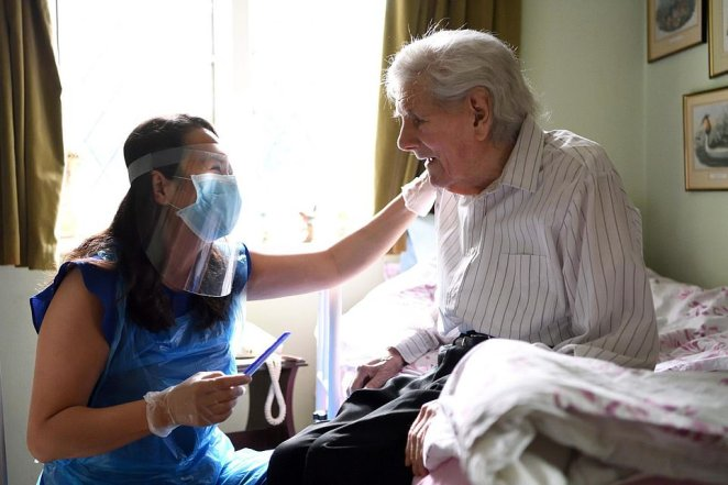 Care Worker by Karwai Tang. A woman wearing personal protective equipment is seen comforting an elderly person