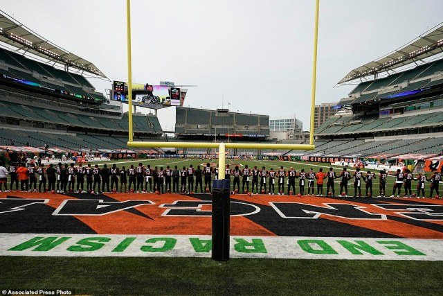 The Cincinnati Bengals stand arm in arm as 'Lift Every Voice and Sing' is played before an NFL football game