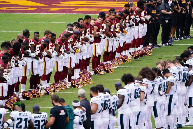 Members of the Washington Football Team and Philadelphia Eagles lock arms and form an oval on the field before the start of an NFL football game on Sunday in Landover, Maryland