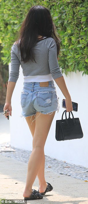 Distressed denim: The 36-year-old actress wore a grey crop top over a plain white tank-top along with distressed denim shorts as she showcased her flat stomach and toned legs.