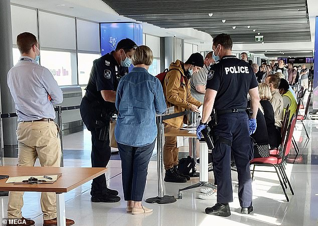 Police and Defence Force present as they checked passengers at Brisbane airport flying in from an Adelaide flight on Sunday