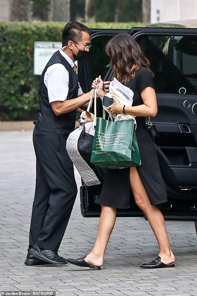 Hotel look:She completed her look with black flat shoes, while carrying several bags, one of which held one of her dogs
