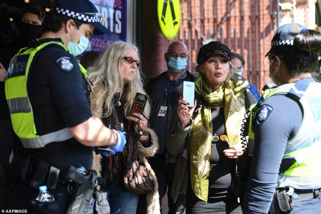 Police question two women during an anti-lockdown rally in Melbourne on Sunday