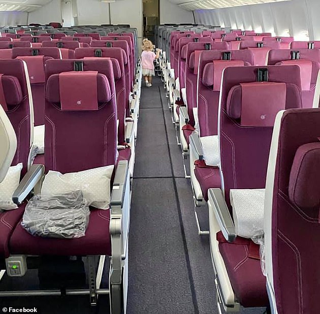 Australians trying to get home have said they were forced to buy business class tickets on planes with just 30 passengers. Here a child plays in the completely empty economy section