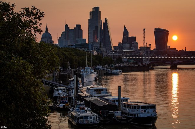 The sun rises behind skyscrapers in the City of London basking the River Thames in a warming gold glow this morning